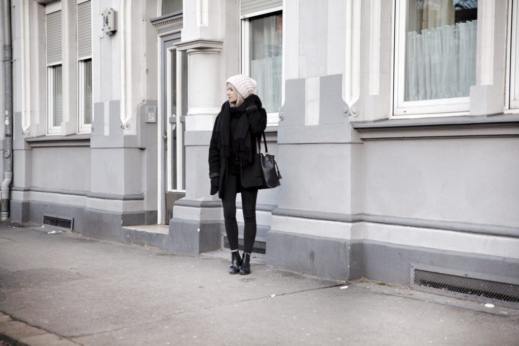 All black outfit with a rosé beanie and black chelsea boots